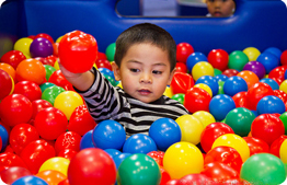 child in ball play area